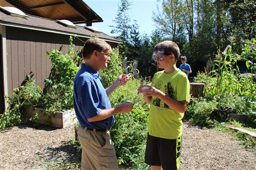 teacher and student discuss lesson in outdoor classroom garden