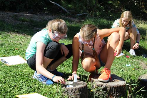 three girls conduct a science experiment with water and containers in the outdoor classroom