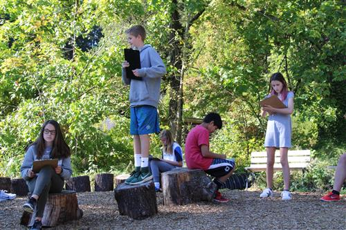 five students with clipboards sit and stand in the outdoor classroom