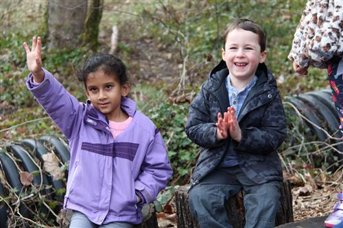 young girl raises hand while young boy claps during an outdoor classroom lesson