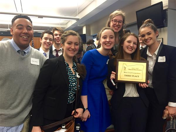 Mock trial team members pose with third place plaque