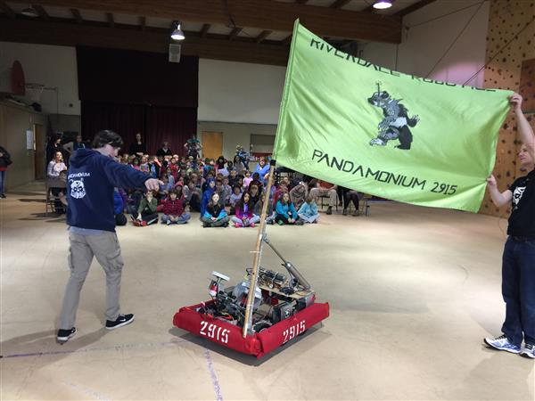 Students demonstrate how robot works in front of young audience