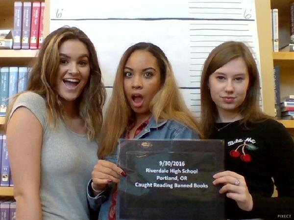 Three students pose in the banned books photo booth