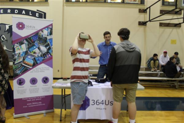students talk with service representative in the gym during Service Learning Fair