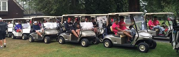 golfers line up in golf carts