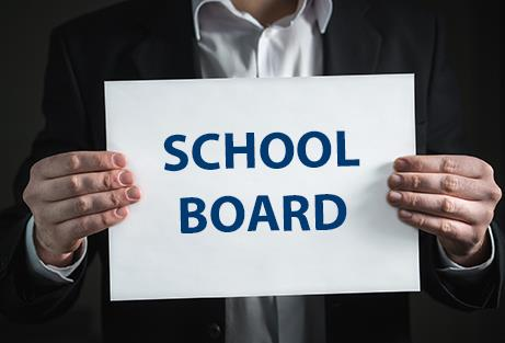 man holding a sign reading School Board