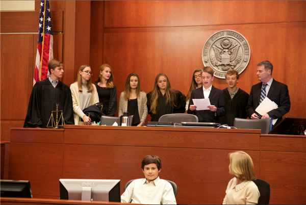 8th grade students standing in a courtroom for Mock Trial