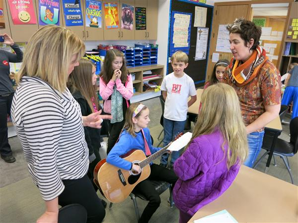 Students sing and play guitar during a class lesson