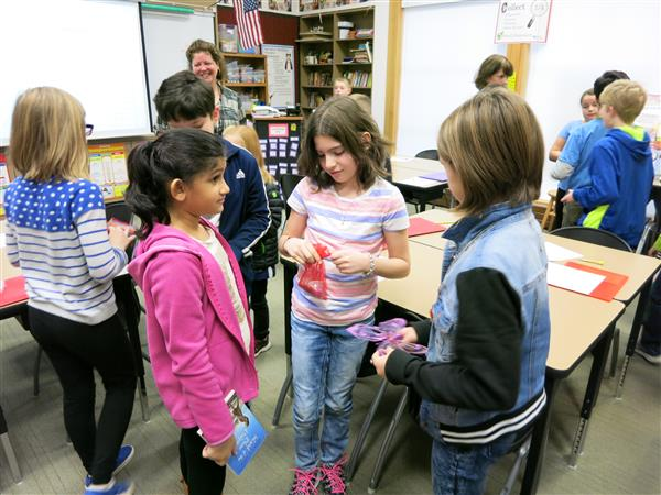 Students exchange items during a classroom lesson in bartering