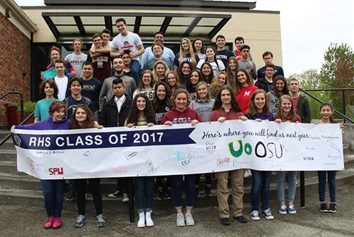 Class of 2017 standing outside school with banner