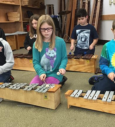 Students learn to play xylophone in music class