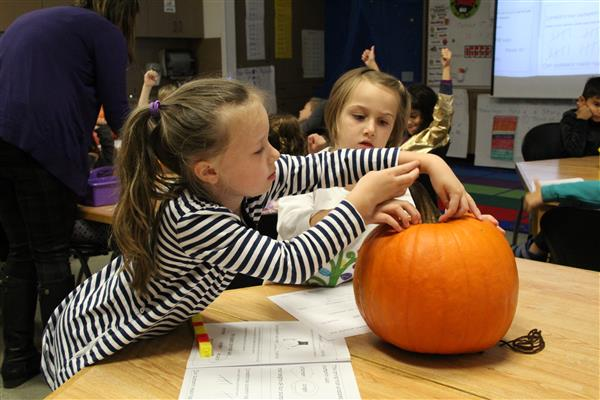 two girls measure a pumpkin
