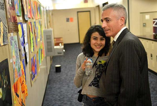 Father and daughter admire art on the walls at Riverdale High School