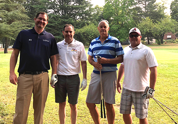 Riverdale's athletic director is joined by coaches, sponsors and golfers at the golf tournament