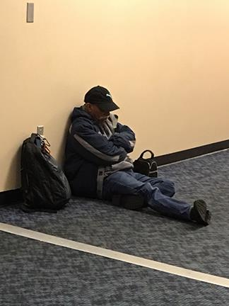 Man who sought shelter at Riverdale High School during the storm takes a nap leaning against the wall