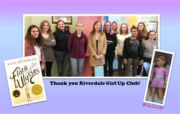 Photo of Riverdale's Girl Up club members, along with the doll and books they gifted a foster child