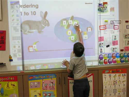 Young student using stylus on interactive white board in class